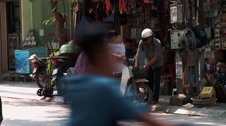 holding onto : Hanoi, Vietnam - 21st October 2019: Vietnamese Locals loads large heavy goods onto a moped