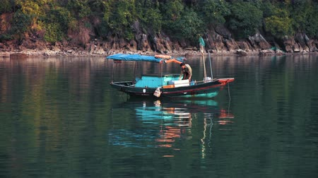 Ha Long Bay, Vietnam - 15th October 2019: A local on a small boat prepares supplies to sell to tourists on passing cruise ships