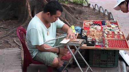 Hanoi, Vietnam - 11th October 2019: A local builds wooden souvenirs for tourists using a hand saw Stock Footage