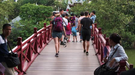 Hanoi, Vietman - October 11th 2019: Crowds of tourists walk over the red Huc Bridge on Hoan Kiem Lake in the capital of Vietnam