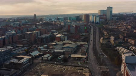 tilt : Sheffield, UK - 1st December 2019: Aerial sunrise reveal of Sheffield City during a frosty winters morning along a busy road Stock Footage