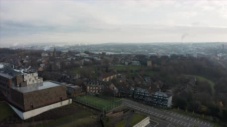 Sheffield, UK - 1st December 2019: Aerial view over Sheffield City, South Yorkshire during a frosty winter morning with chimney smoke in the background Stock Footage