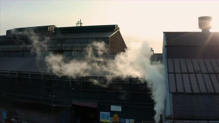 Sheffield, UK - 16th December 2019: Aerial shot of steam in front of Forgemasters steel forge warehouse on the River Don in winter Stock Footage