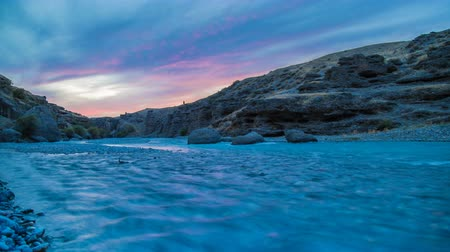 Timelapse. The flow of a wide river in the canyon at sunset. purple clouds reflected in the water. Stock mozgókép