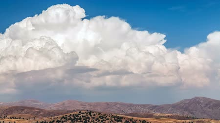 Timelapse. Fluffy white cumulus clouds moving over the mountains of Africa. On a clear sunny day in autumn.