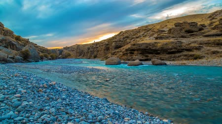 4K Timelapse. Beautiful clouds at sunset moves over the canyon where the river flows