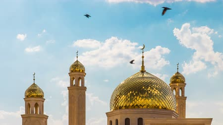 4K Timelapse. Over the golden domes of the mosque Muslim moving clouds and crows fly in a sunny day in the summer.