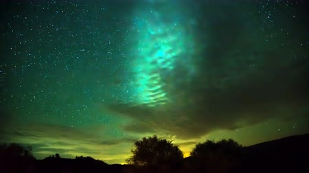 4K Timelapse. The motion of the Milky Way in the night sky. Clouds cover the sky illuminated from below. Stock mozgókép