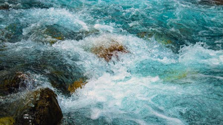 Fast flowing clean clear water boils hitting rocks on a cloudy day in mountain river.