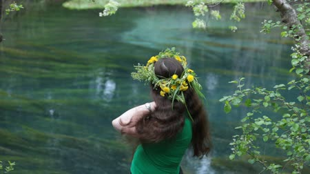 The woman in green combs hair on the river bank. Spring, cloudy weather Stock mozgókép
