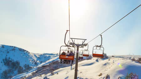 Kazakhstan, Shymkent, FEBRUARY, 9, 2017. Ski lift at the ski resort lifts people on the mountain. In the rays of sunlight