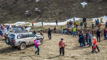 FEBRUARY, 26, 2017 Kazakhstan, Shymkent Russian competitions of off-road cars. The inverted car is pulled out of the ravine by cables, with a large crowd of people. In early spring