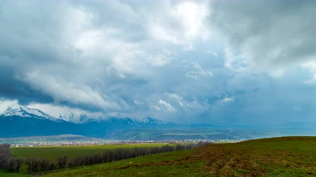 4K Timelapse. Winter clouds above the spring fields, foothills of the western Tien shan
