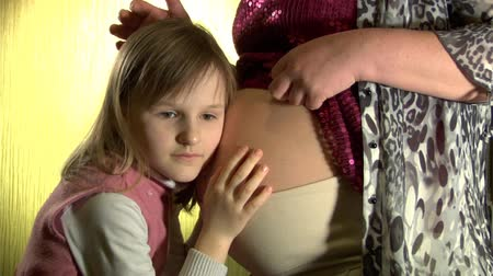 rodzeństwo : girl listens to her future sister in mothers belly
