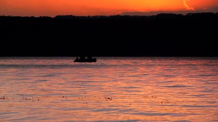 водохранилище : a beautiful sunset over the water and fishers boat silhouette. Bakota bay (Dnistrovske reservoir), Dnister river, Podilski tovtry National park, Khmelnitskiy region of Western Ukraine