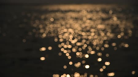 блестки : Bokeh of sunset light reflect on wave at sea (Blurred background) Стоковые видеозаписи