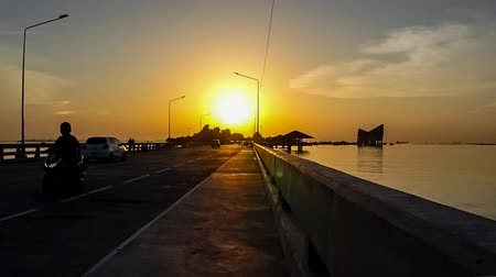 dark island : Time lapse of sunset sky at Koh Loy island with silhouette of traffic on bridge, Sriracha city, Chonburi, Thailand