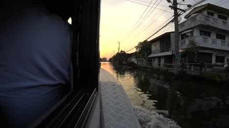 motorcycles : BANGKOK, THAILAND - 18 DEC : View from passenger boat with sunset sky on 18 December 2017 in Phasi Charoen canal, Bangkok, Thailand Stock Footage