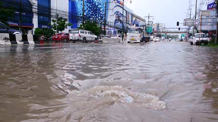 CHONBURI, THAILAND - 7 JUNE : Flood water flow through rain drain at road on 7 June 2019 in Sriracha, Chonburi, Thailand