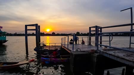 cauda : BANGKOK, THAILAND - 11 JULY : Time lapse of sunset at Bangna ferry port at Chao phraya river on 11 July 2019 in Bangkok, Thailand