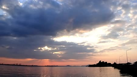 Time lapse of clouds with sunset sky at sea and island silhouette foreground