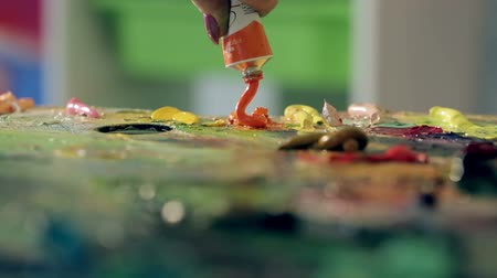 oilpaint : Artist squeezes orange paint on the palette Stock Footage