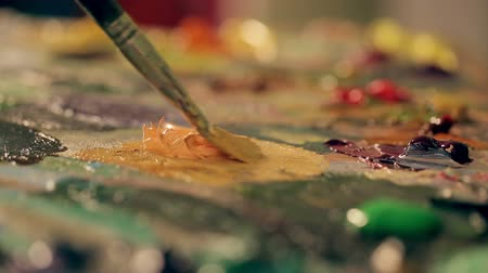artistas : The artist mixes oil orange paint on a palette close up