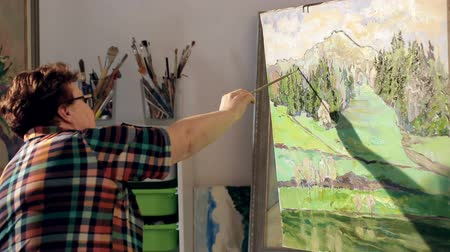 expressionism : Artist paints a picture of oil paint brush in hand with palette
