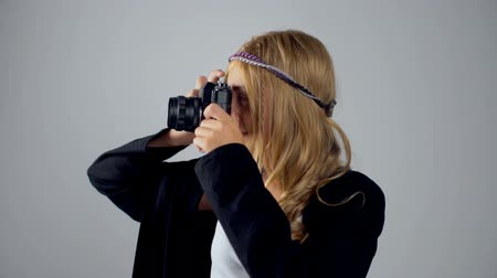 vintage film : Cute blonde young girl holding an camera isolated on gray background. A teenager is smiling and taking pictures