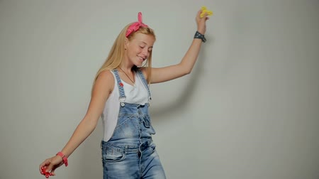 Happy young girl in denim shirt dancing and looking at the camera.