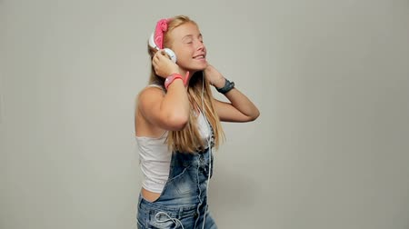 contemporâneo : Portrait of a beautiful young girl (woman) listening to music, dancing, happy smiling.