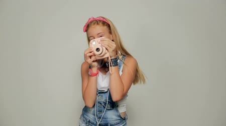 Young hipster woman holding retor instant camera taking photo portrait.