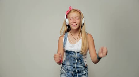 Happy girl dancing and listening to the music isolated on a white background.