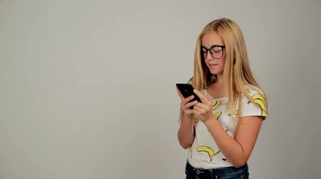 Cute young woman texting on her phone wearing glasses in studio on white background