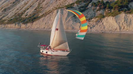 turizm : A white yacht under a black and white sail with a crew sails calmly along the blue sea along a mountainous shore. Stok Video