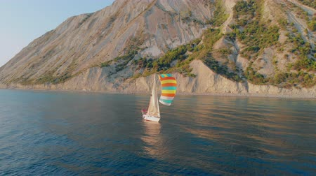 A white yacht under a black and white sail with a crew sails calmly along the blue sea along a mountainous shore. Stock Footage