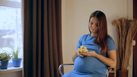 Pregnant Happy Woman holding Baby Shoes in her Hands. Mom Expecting her Baby. Pregnant Woman Belly. Pregnancy. Maternity concept