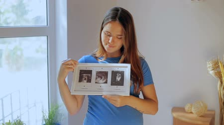 Pregnant woman looking at her babies first sonography results. Stock Footage