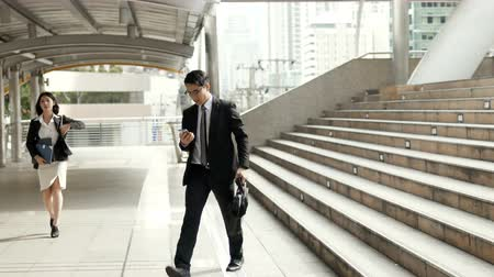Asian businessman walking down stairs and talking with smartphone and young female worker walk straight out the other side and see watch, Both have rushed due to late in the morning, business concept