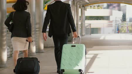lobby : Dolly shot behind the businessman and pretty businesswoman walking and talking together, They are dragging a baggage with wheel along the passageway and turn left