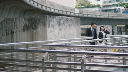 Two Asian colleagues carry bag  and holding the document file and walk up the bridge to go to the nearest sky train station. man watch wristwatch, and the Sky train runs through Skyscraper Vídeos