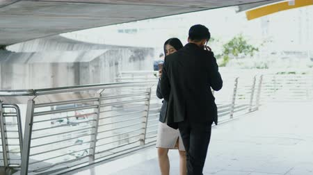 Dolly shot with scene of businessman walking and talk with smartphone going in the opposite direction with woman, accident bumped into each other on the bridge and In hand dropped on the floor Vídeos