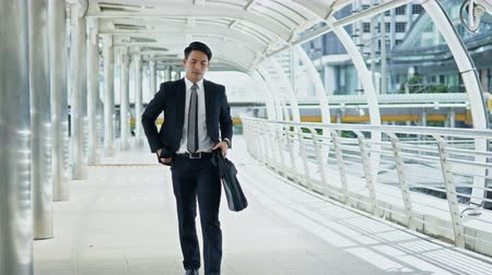 Dolly shot scene Young businessman hold a briefcase, watch wristwatch and stopping to pick up the smartphone on walkway on bridge Vídeos