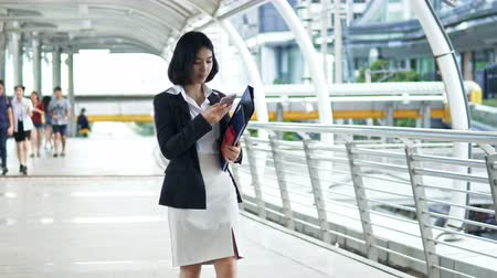 Pretty businesswoman hold document folder in arm, walk and stopping to pick up the phone, then she talking and walk through the camera, and See the back of the businessman going in opposite direction