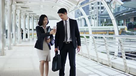 The businessman and pretty businesswoman walking and talking together, They are checking map in smartphone and walk through the camera