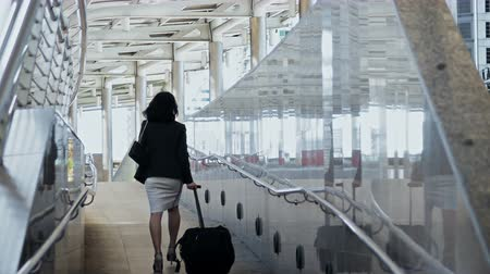 Locked shot with scene to back of young business woman walks along the baggage with haste, checking time with a wristwatch, moving on with hastiness