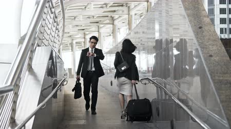 Dolly shot with Young businesswoman dragging baggage going up step floor and smart businessman walking in the opposite direction in rush hour Vídeos