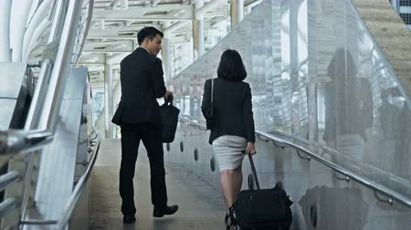 dragging : Dolly shot with behind of the businessman hold briefcase  and pretty businesswoman dragging a baggage, they are walking and talking together Stock Footage