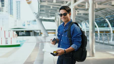 Locked shot with Asian Handsome young man wearing a shirt jeans and sunglasses holding paper map and smartphone in left hand and thump up the right hand and smile to camera Vídeos