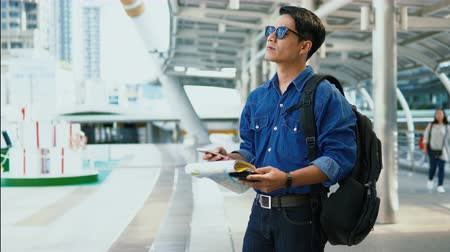 Dolly and close up Asian handsome young man wearing a shirt jeans and sunglasses is checking point on paper map and smartphone before deciding which way to go Vídeos